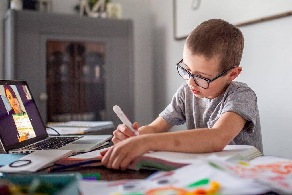boy working on school work while video conferencing